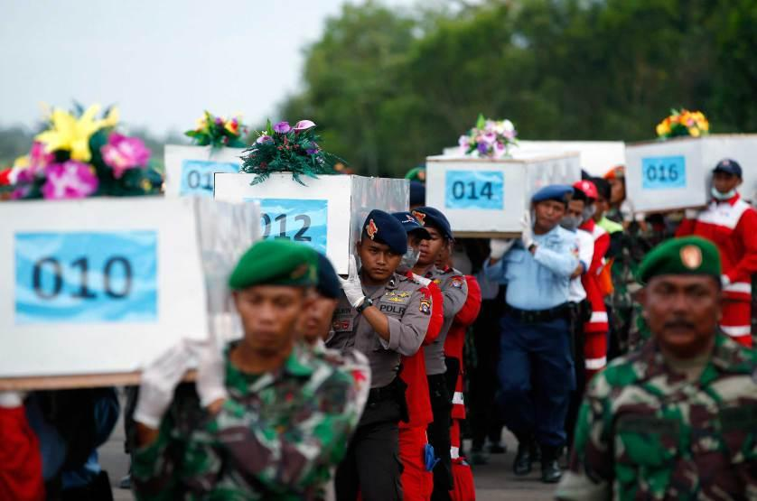 Caskets containing the remains of AirAsia QZ8501 passengers recovered from the sea are carried to a military transport plane at the airport in Pangkalan Bun