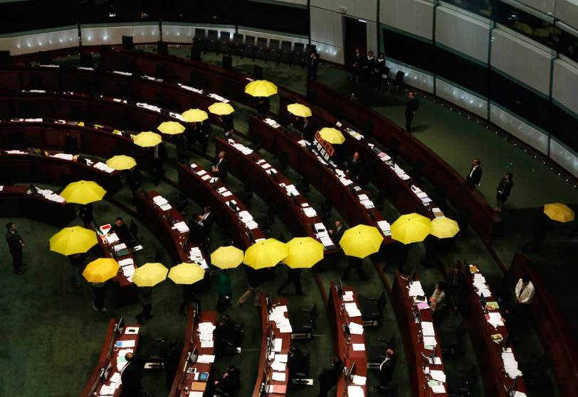 Pro-democracy lawmakers carrying yellow umbrellas, symbols for Occupy Central movement, leave in the middle of Legislative Council meeting as gesture to boycott government in Hong Kong